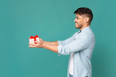 Cheerful guy offering gift box wrapped with red ribbon and bow. Turquoise studio background, free space.