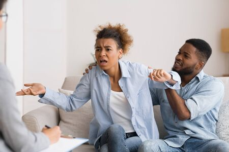Misunderstanding in relationship. Angry african american wife blaming her frustrated husband on therapy session. Free Space