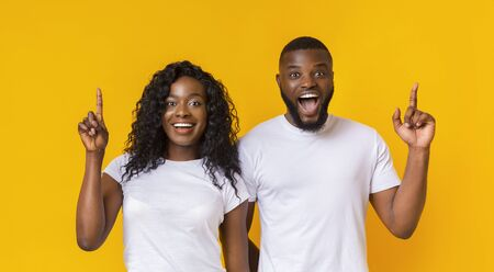 Surprised Black Guy And Girl Pointing Fingers Upward, yellow studio background