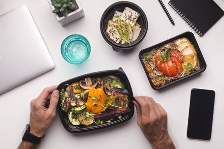 Entrega online. Hombre comiendo alimentos saludables durante la hora del almuerzo en la oficina, teléfono móvil con pantalla en blanco