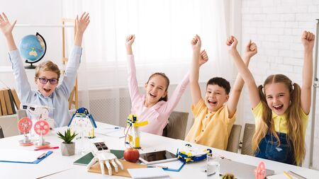 Stem education. Happy children with raised hands celebrating success after robotics class Stock Photo