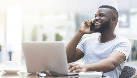 Cheerful african guy talking by cellphone while typing on laptop and widely smiling, panorama, copy space
