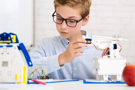 Schoolboy constructing electronic robot, working on new project at stem lab