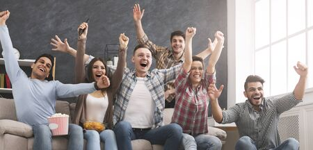 Friends watching football at home and yelling goal with raised hands, panorama with free space