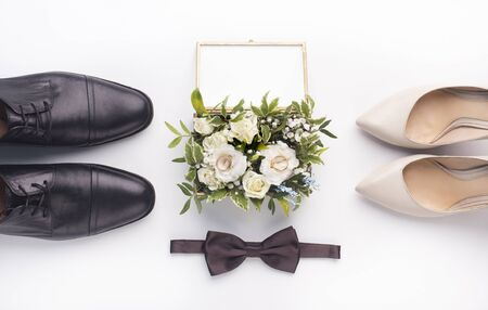 Bride and groom accessories. Wedding shoes, bow-tie and bouquet on white background, panorama