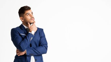 Young Hispanic Businessman Touching His Chin Thoughtfully On White Background. Strategic Thinking Concept. Panorama, Empty Space