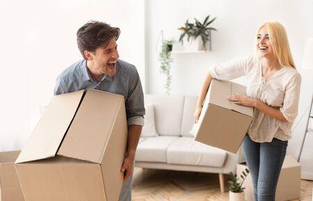 Pareja llevando cajas de cartón y riendo mientras se muda a un nuevo piso o casa. Panorama, espacio vacío
