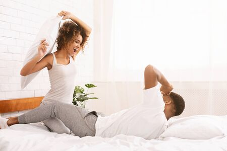 Cheerful african couple is fighting by pillows in bed, having fun together, empty space Stock Photo