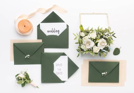 Wedding planning. Stylish green envelopes with save the date text on invitation cards and accessories on white background