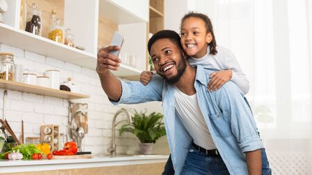 So happy together. Black man and his little girl taking selfie on cellphone, cooking together in kitchen, panorama