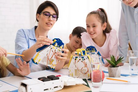 Stem education. Kids constructing robots with teacher, woman explaining new material to children