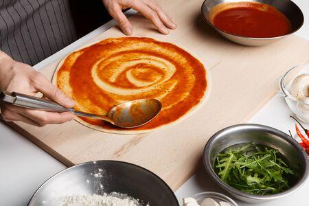 Przygotowanie pizzy. Szef Kuchni smarujący sos pomidorowy na spodzie pizzy, gotujący w pizzerii