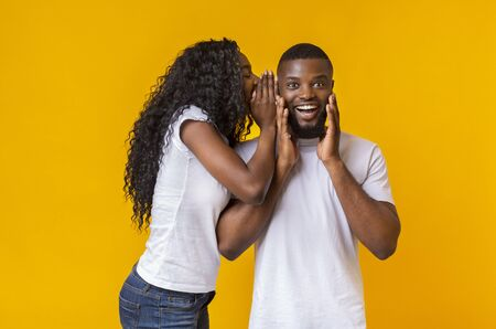 African American Woman Sharing Secret With Her Man, guy is excited, yellow studio background