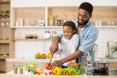 African American Man Teaching His Daughter To Cut Vegetables, kitchen interior, copy space