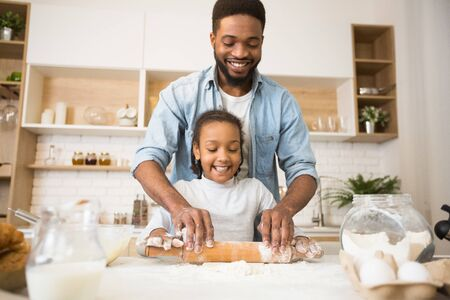 Happy Afro Man And His Daughter Rolling Dough Together, kitchen interior, copy space