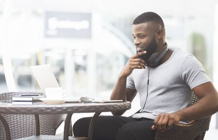 African guy thinking about what to choose on laptop screen in cafe, copy space
