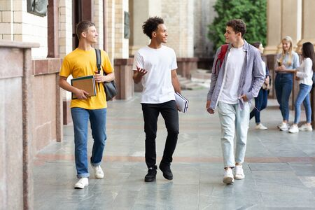College students walking in campus and chatting during break outdoors