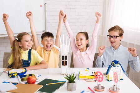 Children celebrating success after doing robots at stem lesson, early education concept Reklamní fotografie