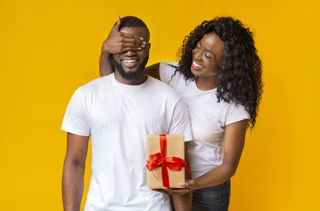 Attractive Black Woman Closing Her Man Eyes, holding gift for him, yellow background