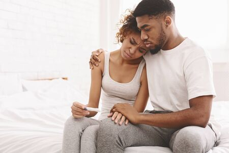 Infertility problem. Upset african american couple sitting on bed with negative pregnancy test result, free space