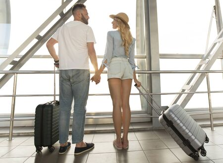 여행 개념입니다. 국제 공항 터미널의 창 근처에 서 있는 사랑스러운 커플, 뒷모습
