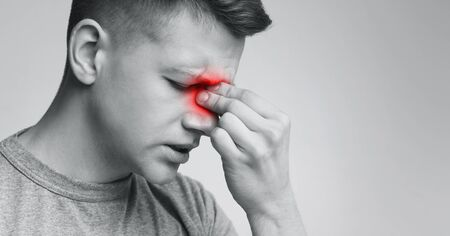 Sinus pain, sinusitis. Upset man holding his inflamed nose, black and white photo with red sore zone, panorama with free space