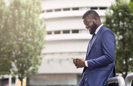 Attractive happy businessman is texting on cell phone near modern office building, side view with copy space. Business, technology and communication concept