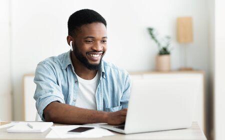 Homme afro-américain souriant dans des écouteurs étudiant une langue étrangère en ligne via une application de vidéoconférence, panorama avec espace de copie