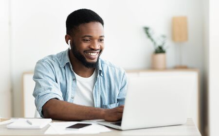 Smiling african-american guy in earphones studying foreign language online through video conference application, panorama with copy space