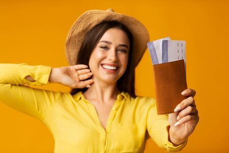 Happy tourist. Millennial girl posing with passport and tickets on yellow studio background Foto de archivo