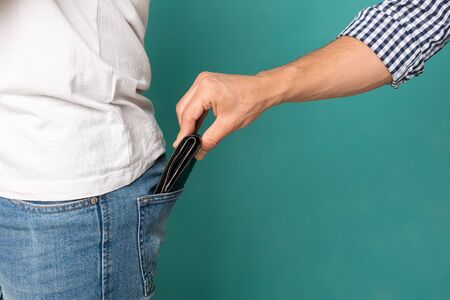 Pickpocketing And Theft. Man Stealing Wallet From Jeans Back Pocket On Turquoise Studio Background. Closeup, Free Space. Archivio Fotografico