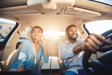 Enjoying travel. Excited african couple driving car and smiling, copy space