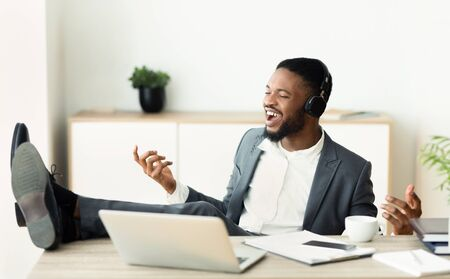 Handsome african businessman listening music imagining that he is rockstar, putting his legs on table and playing on virtual guitar. Copy space