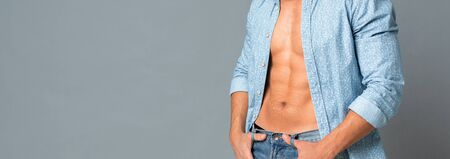 Muscular Male Model In Unbuttoned Shirt Showing His Naked Torso And Perfect Abs. Panorama, Cropped, Free Space Stock Photo