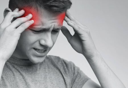Young man suffering from strong headache touching his temples, emotional black and white photo with red sore zones