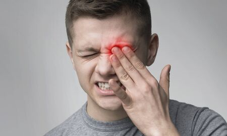 Upset man suffering from strong eye pain. Healthcare concept, panorama