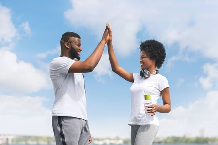 Couple Losing Weight Together. Fit Afro Man And Woman Giving High Five After Morning Jogging Near River. Panorama Banque d'images