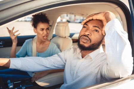 Missed road. Afro couple arguing during their journey in car, frustrated man looking aside