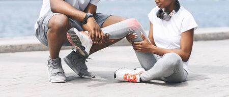 Jogging Injury. Black Man Helping Woman Runner With Injured Knee Near River. Cropped, Panorama Banque d'images