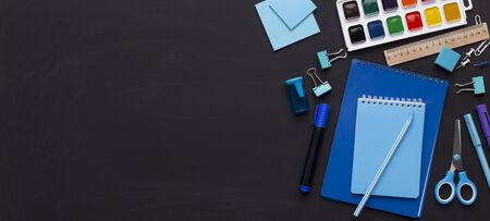 Perfectionism concept. Blue colored school stationery on black board with copy space, panorama