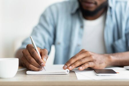 Unrecognizable African American Self-Employee Writing Down His Plans To Notepad. Closeup with copy space Banco de Imagens