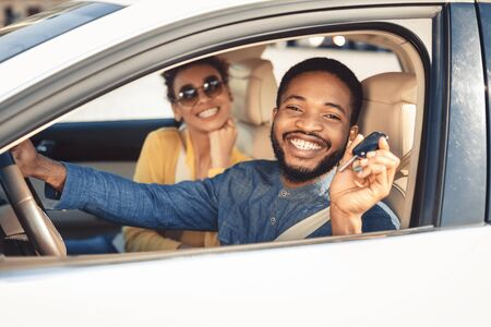 Visiting car dealership. Afro couple showing car key, looking at camera and smiling, sitting in new car Stockfoto