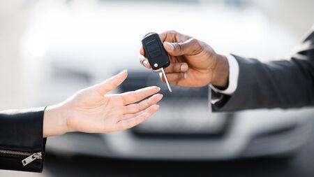 Car sale. Dealer giving key to new owner in auto show or salon, closeup Reklamní fotografie