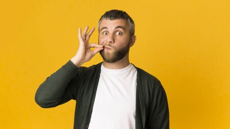 Be quiet. Middle-aged man zipping his mouth on yellow background, using sign language, copy space
