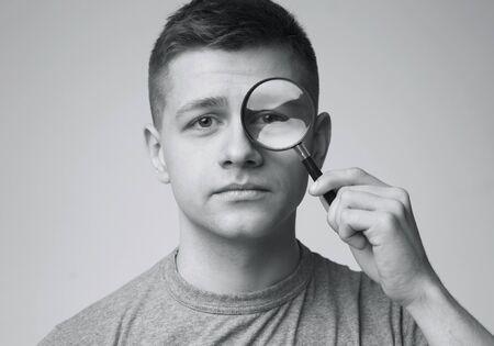 Portret van een jonge man die door vergrootglas kijkt, zwart-wit foto Stockfoto