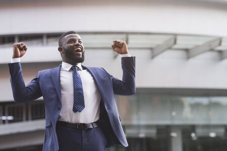 Happy excited black businessman celebrate victory with fists raised in the air staying against modern glass office center background, lifestyle portrait Banco de Imagens