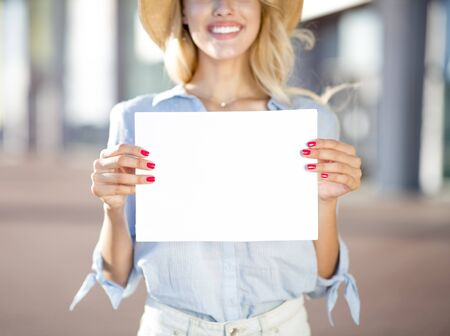 Pretty woman holding empty placard outside the airport, copy space for text 免版税图像