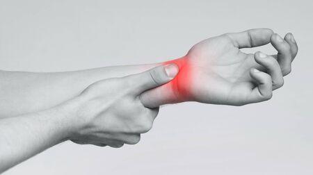 Carpal tunnel pain. Man massaging painful wrist, monochrome panorama photo
