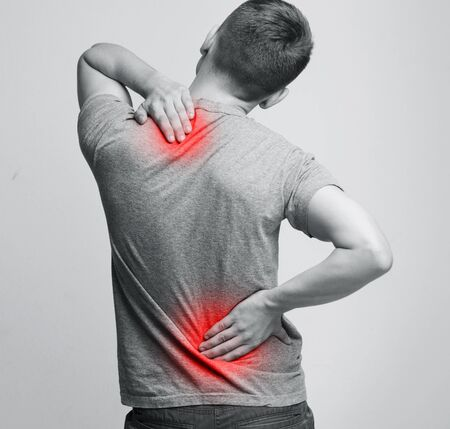 Man with neck and back pain, rubbing his painful body, back view Stockfoto