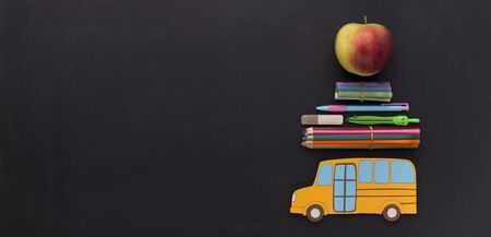 Yellow school bus with stationery and apple going to the september, panorama, copy space